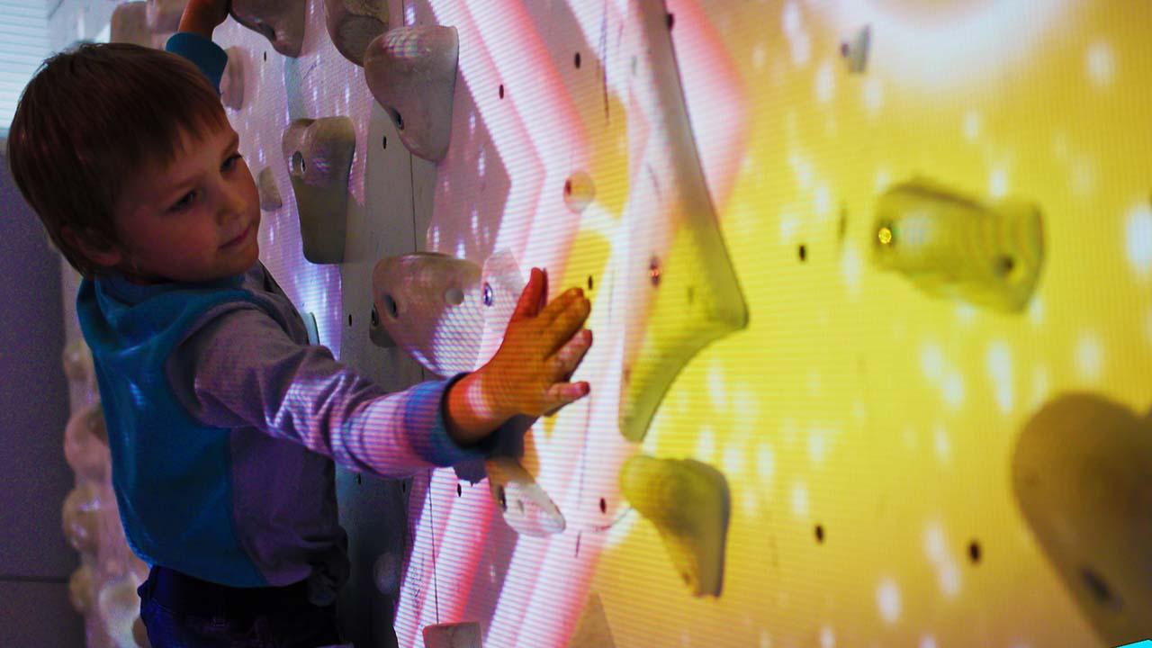 enfant jouant au mur de grimpe en réalité augmentée - valoclimb
