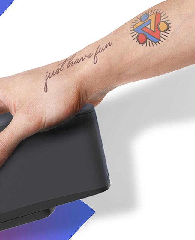 bras tatoué tenant une imprimante à tatouages éphémères - vaud valais genève fribourg